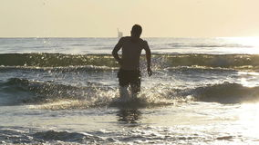 Fit man running out of sea water in slow motion at twilight. Man running out of sea water in slow motion at twilight stock video