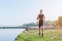 Fit man running outdoor in nature on beach Morning training. Royalty Free Stock Image