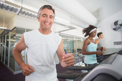 Fit man running on treadmill listening to music Royalty Free Stock Photo