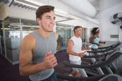 Fit man running on treadmill listening to music Stock Images