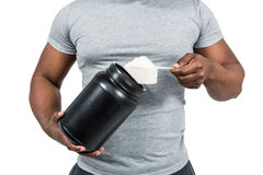 Fit man scooping protein powder Royalty Free Stock Images