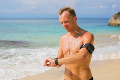 Fit man setting his smartwatch before training on te beach. Fit young man setting his smartwatch before training on te beach Stock Images
