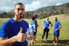Fit man showing thumbs up while holding water bottle Stock Photo