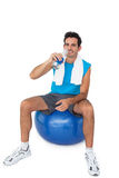Fit man sitting on exercise ball while drinking water Royalty Free Stock Photography