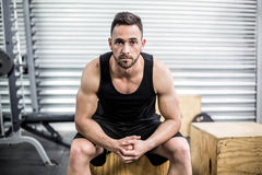 Fit man sitting on wooden box Royalty Free Stock Images