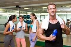 Fit man smiling at camera in busy fitness studio Royalty Free Stock Photography