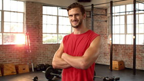 Fit man smiling at camera in fitness studio. In slow motion stock video