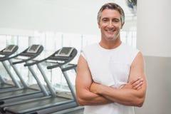 Fit man smiling at camera beside treadmills Stock Image