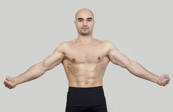 Fit man spreading arms showing his body. Royalty Free Stock Photos