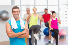 Fit man standing arms crossed at gym. Portrait of fit men standing arms crossed with people exercising in background at gym Stock Photos