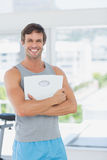Fit man standing with scale in bright exercise room Royalty Free Stock Photos