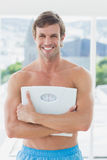 Fit man standing with scale in exercise room Stock Photo