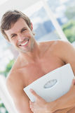 Fit man standing with scale in exercise room Royalty Free Stock Image