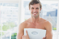 Fit man standing with scale in exercise room Royalty Free Stock Photography