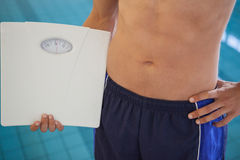 Fit man in swimming trunks standing by the pool holding weighing scales. At the leisure center Royalty Free Stock Photo