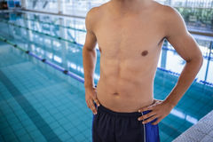 Fit man in swimming trunks standing by the pool. At the leisure center Stock Photo