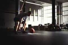 Man training with heavy medicine ball in gym Stock Photography