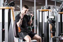 Fit man training on modern machine and working out in gym room Stock Image