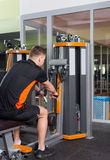 Fit man training on row machine in gym Stock Photos