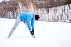 Fit man training and stretching outdoor in snow on a cold day Stock Photo