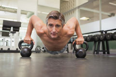 Fit man using kettlebells in his workout Stock Images