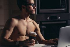 Fit Man Using Laptop and drink coffee at morning Stock Photography