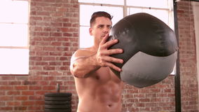 Fit man using medicine ball in gym stock footage