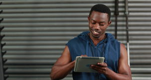 Fit man using tablet and smiling at the camera stock video footage