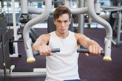 Fit man using weights machine for arms Royalty Free Stock Photography
