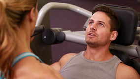 Fit man using weights machine for arms with his trainer Stock Photo