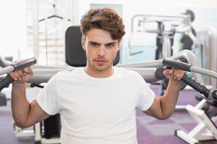 Fit man using weights machine for arms looking at camera Stock Images