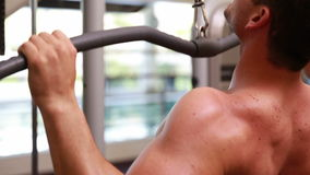 Fit man using the weights machine for his arms Royalty Free Stock Photography