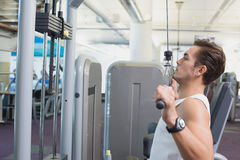 Fit man using the weights machine for his arms Stock Photo