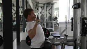 Fit man using the weights machine for his arms at the gym stock video footage