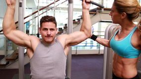 Fit man using the weights machine for his arms while trainer supervises Royalty Free Stock Photography