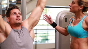 Fit man using the weights machine for his arms while trainer supervises Stock Photos