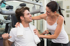 Fit man using weights machine with trainer encouraging him Royalty Free Stock Photos