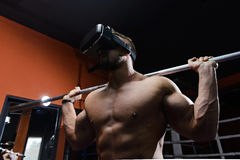 Fit man during virtual workout. Young muscular man with vr headset and with barbell on shoulders during indoor workout in gym.Selective focus Royalty Free Stock Images