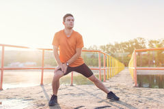 Fit man warming up doing lunges exercising during morning run. Fit man warming up doing lunges exercising during morning run Stock Images