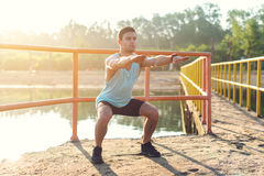 Fit man warming up doing squats stretching arms forward outdoors. Fit man warming up doing squats stretching arms forward outdoors stock photography