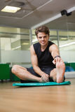 Fit man warming up in fitness studio Stock Photo