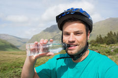 Fit man wearing bike helmet drinking water Royalty Free Stock Photo