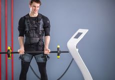 Man working out EMS training with barbell closeup, power pose. Fit Man wearing black electrostimulation suit lifting barbell closeup, power pose Royalty Free Stock Photos