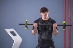 Man working out EMS training with barbell closeup, power pose. Fit Man wearing black electrostimulation suit lifting barbell closeup, power pose Stock Photos