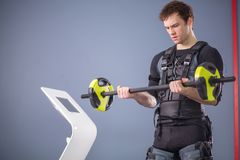 Man working out EMS training with barbell closeup, power pose. Fit Man wearing black electrostimulation suit lifting barbell closeup, power pose Royalty Free Stock Photo