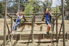 Fit man and woman climbing down the rope during obstacle course. Fit men and women climbing down the rope during obstacle course in boot camp royalty free stock photo