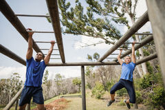 Fit man and woman climbing monkey bars during obstacle course Stock Photos
