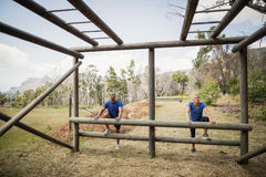 Fit man and woman climbing monkey bars during obstacle course. Fit men and women climbing monkey bars during obstacle course in boot camp stock photos