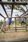Fit man and woman climbing monkey bars during obstacle course. Fit men and women climbing monkey bars during obstacle course in boot camp stock images