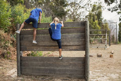 Fit man and woman climbing over wooden wall during obstacle course. Fit men and women climbing over wooden wall during obstacle course in boot camp royalty free stock image